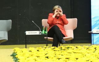 Tallinnas viibinud Angela Merkel piilub ajakirjanikke ja kolleege läbi sõrmebinoklite.