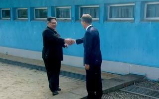 Kim Jong-un ja Moon Jae-in suruvad kätt üle kaht Koread lahutava demarkatsioonijoone.