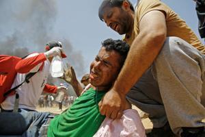 Palestiina meeleavaldaja aitab viga saanud protestijat.