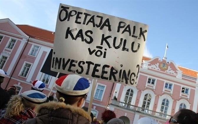'Is a teacher's salary an expense or an investment?' asks this sign at a rally at the Parliament building.