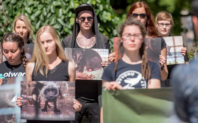 People holding signs at a protest against fur farming.