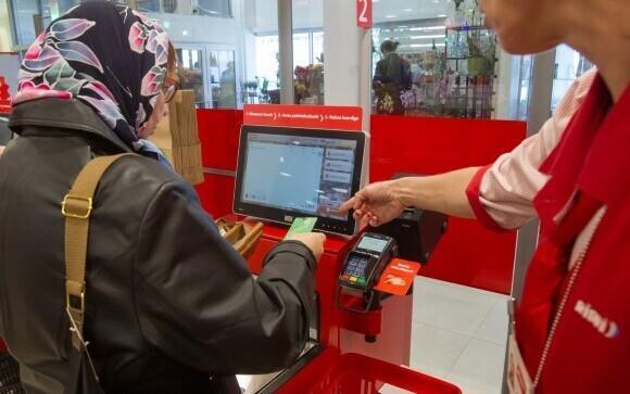 A Rimi employee helping a customer use self-checkout.
