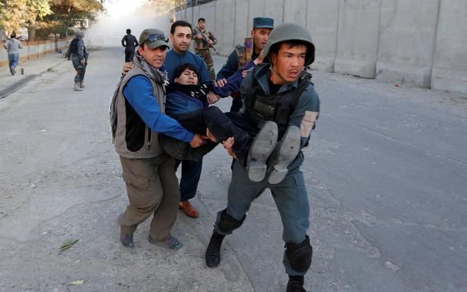 Afganistani politseinikud kannavad plahvatuse järel vigastatut.
