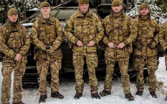 Members of 1 YORKS standing in front of a Warrior tracked armoured vehicle.