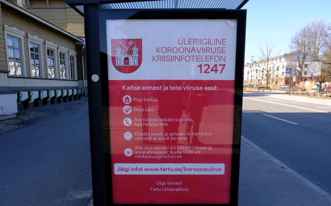 Bus stop ad in front of Tartu Railway Station with coronavirus-related information and contacts.