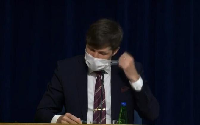 Finance minister Martin Helme (EKRE) getting rid of a face mask before speaking at an April press conference. His government have said that wearing masks will not be obligatory in Estonia.