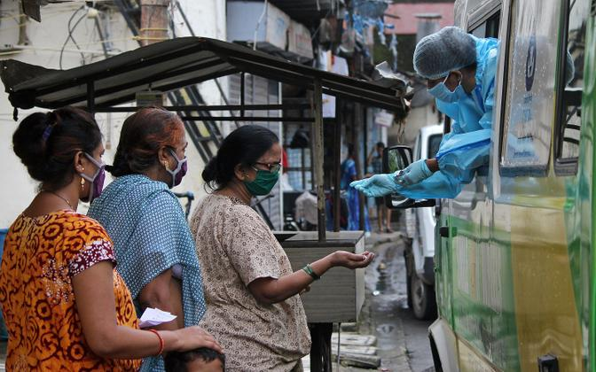 Meditsiinitöötaja väljastab India naistele koroonaviiruse vastaseid ravimeid.