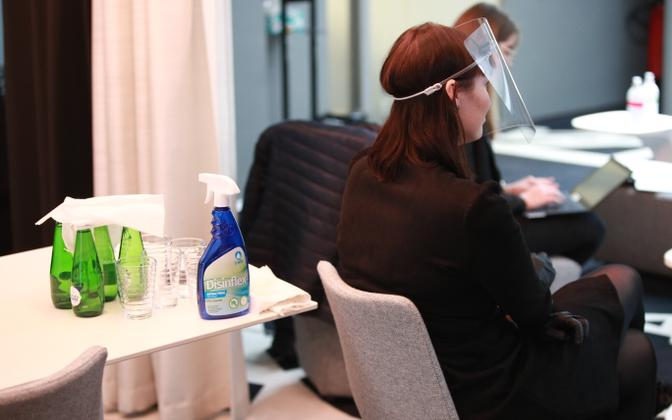Disinfectant and a woman wearing a visor at a Tallinn City Government press conference.