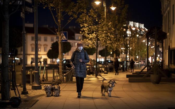 Maskis naine Vilniuse tühjal tänaval koeri jalutamas.