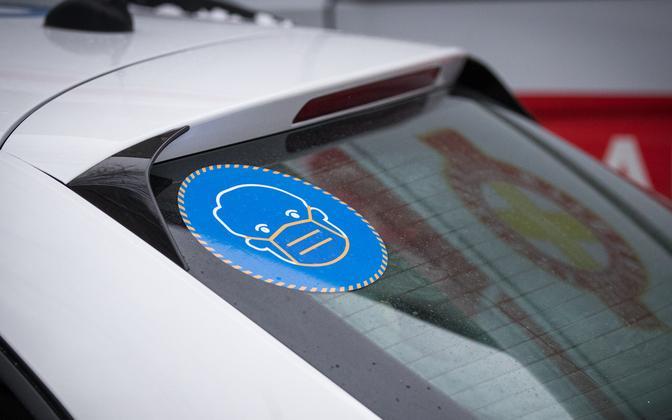 A coronavirus advisory sign on a police car.