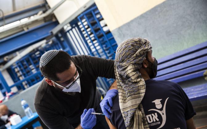 Iisraelis töötav palestiinlane saab vaktsiini Meitari piiripunktis Läänekalda ja Iisraeli territooriumi vahel.