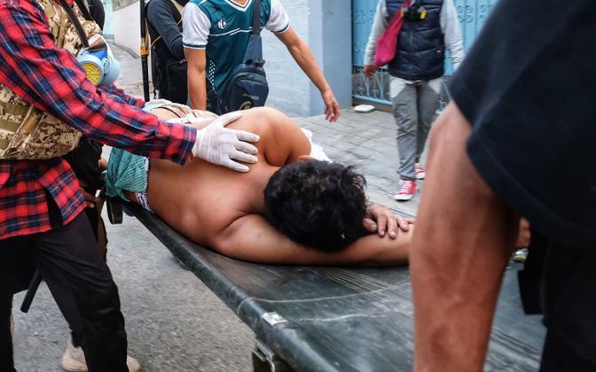 Haavatud meeleavaldaja äraviimine tänavaprotestilt.