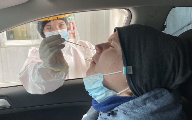 A nurse administering a PCR coronavirus test.