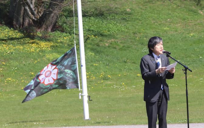 Посол Японии в Эстонии Хажиме Китаока на фоне флага Страны растений.