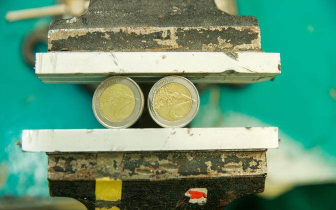 Two two-euro coins in a vice (photo is illustrative).