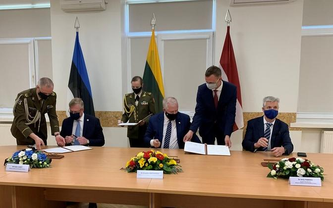 The three Baltic defense ministers, from left Kalle Laanet (Estonia), Arvydas Anušauskas (Lithuania) and Artis Pabriks (Latvia) signing the joint communique on defense, in Šiauliai, Lithuania, Friday May 21.