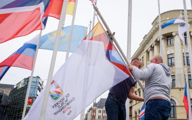 Töölised võtavad Riias maha IIHF-i lipud ja asendavad need Riia linna omadega.