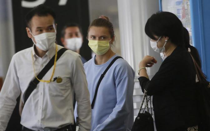 Kristsina Tsimanovskaja (kollase maskiga) Narita lennujaamas