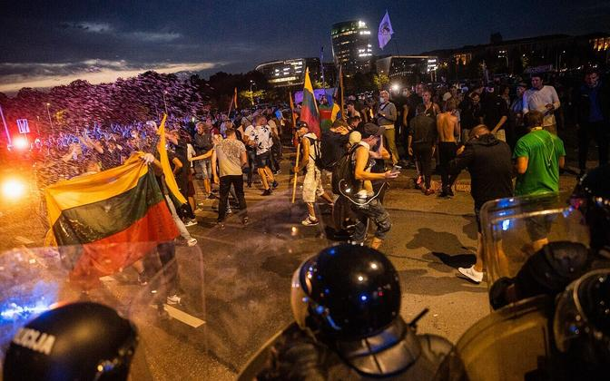 Lithuanian riot police face anti-lockdown protesters in Vilnius, on the evening of Tuesday, August 10.