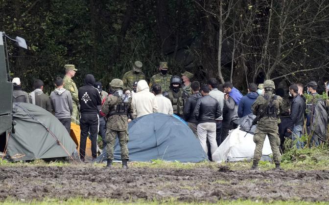 Poola piirivalvurid tabatud immigrantide rühma valvamas.